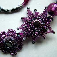 Lynn Davy beading. Purple Passion choker. Featuring rich plum coloured Murano glass, gemstone chips and a variety of beads in a freeform design decorated with brickstitched flowers. The beaded toggles fasten together with a pretty butterfly loop. There is a matching bracelet and a set of flower earrings.