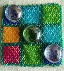 Lynn Davy beading, Noughts and Crosses set.  Symmetrical netting board with glass playing pieces.