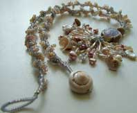 Lynn Davy Beading - Beading Gallery - Photography by Joanna Bury. Dawn Strandline  A peyote spiral in muted colors complements the lampwork focal by Vicki Honeywill. An abundance of seashell curls emphasizes the seaside theme!  click on thumbnail to see larger image
