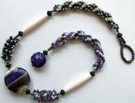 Lynn Davy Beading - Beading Gallery - Photography by Joanna Bury. Purple Zebra Choker   Another project scheduled for Bead magazine, this time with a chunky lentil by beadmaker Claire Morris (Rowanberry Glass Art) perfectly set off by 'caterpillar' and spiral sections in a formal but asymmetric design   click on thumbnail to see larger image