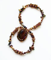 Lynn Davy Beading - Beading Gallery - Photography by Joanna Bury. Tigereye pendant  A gorgeous chunky tigereye cabochon captured in seed beads and hung from a necklace of beaded beads and tigereye chips; a proposed new kit design for Westcoast Jewellery   click on thumbnail to see larger image
